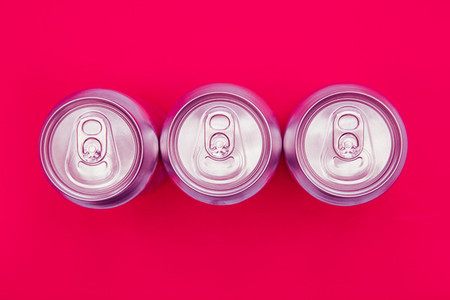 Silver metal energy drinks cans on pink background