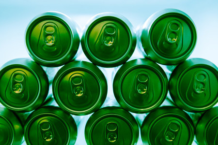 Cold green energy drinks cans in fridge at night