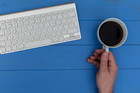 Man holding coffee cup by computer in office workspace
