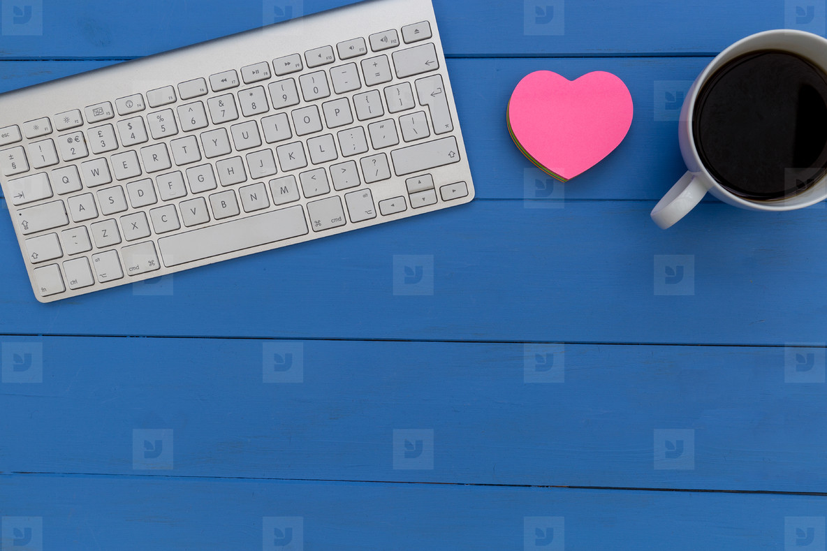 Wireless computer keyboard coffee and love heart on blue wood de