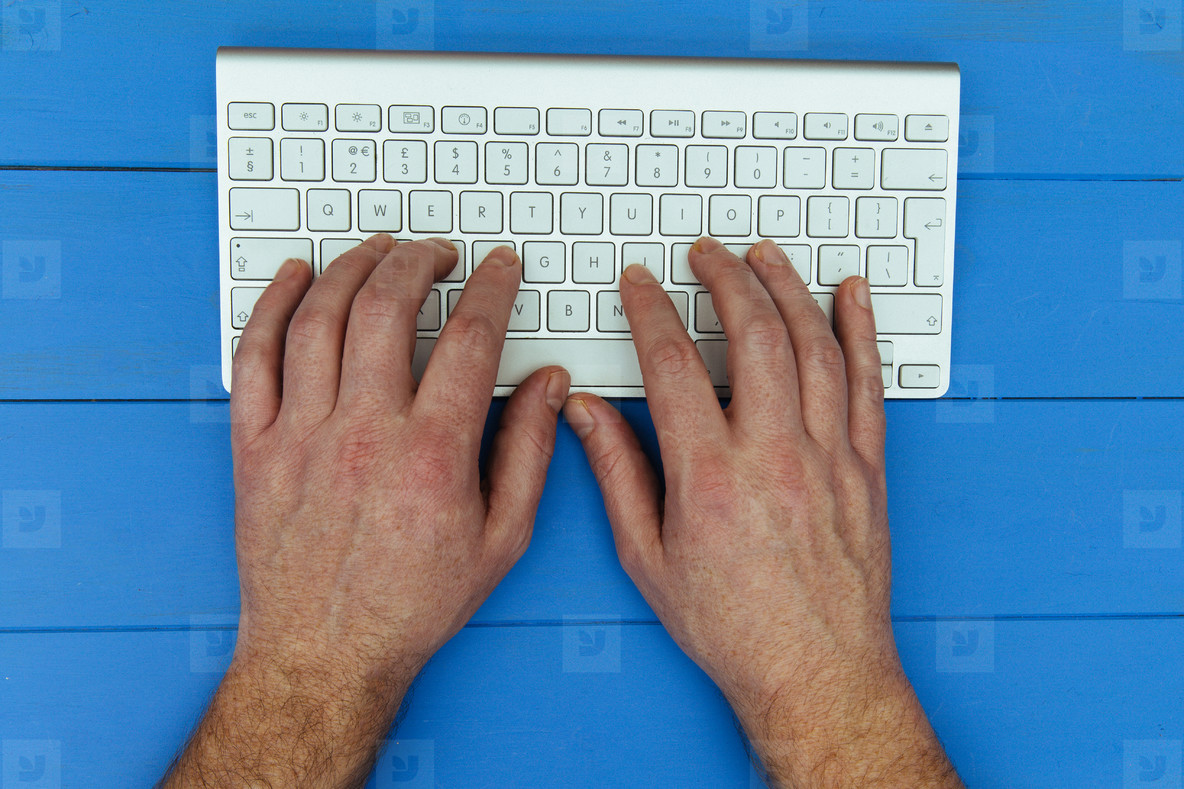 Man typing on wireless computer keyboard on blue wood desk