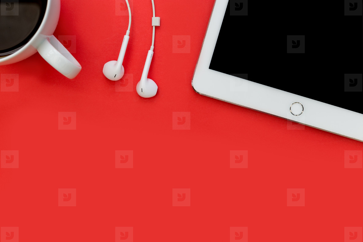 White tablet computer earphones and coffee cup on bright red bac