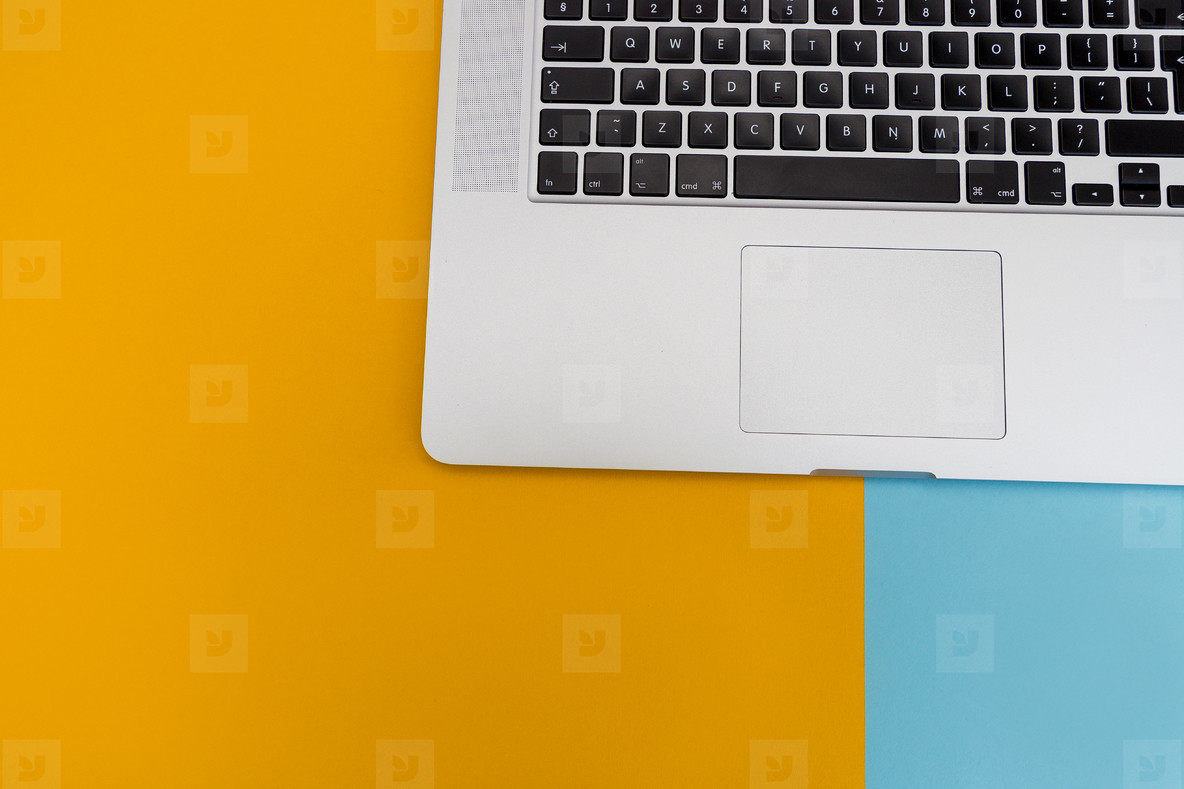Laptop computer keyboard on bright yellow and blue background wi