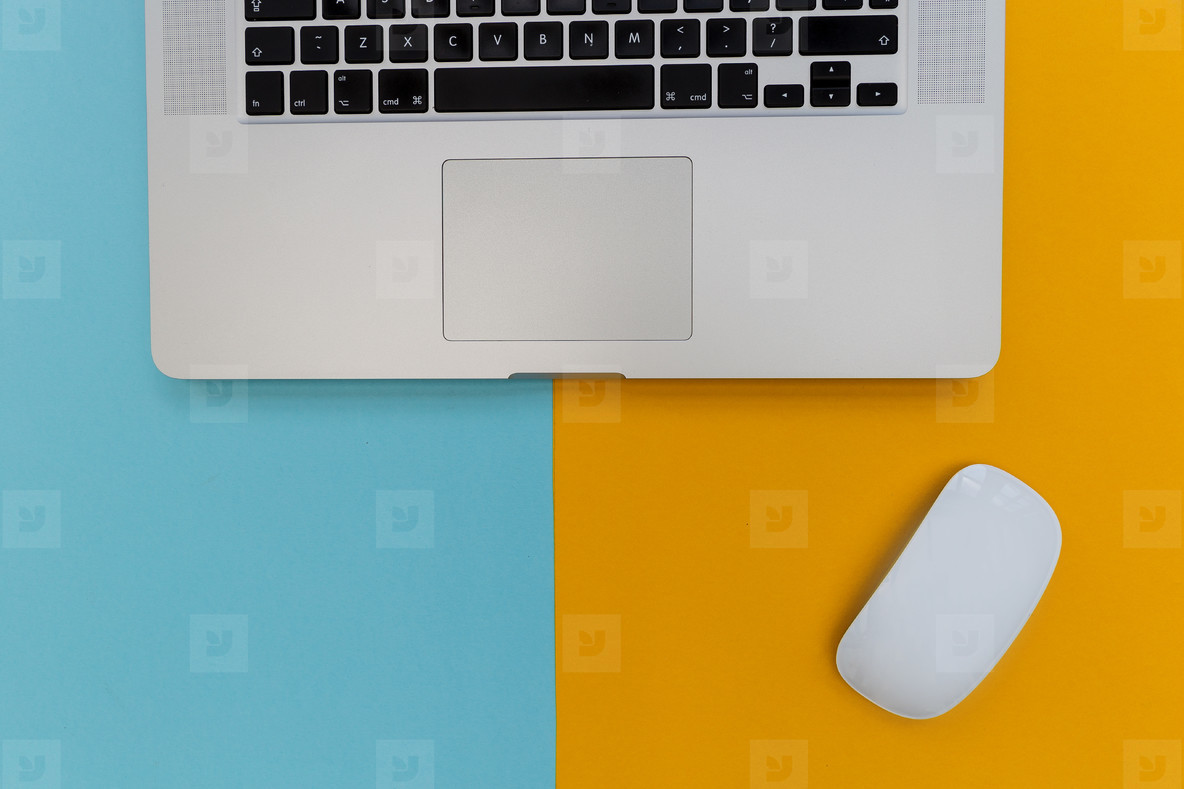 Laptop computer keyboard with mouse on bright yellow and blue ba