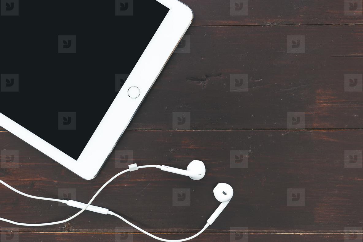 White tablet computer music earphones on dark brown table backgr