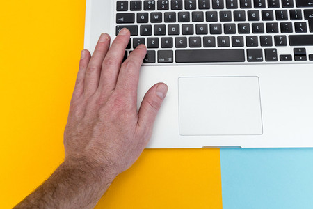 Mans hand typing on laptop computer keyboard on bright yellow a