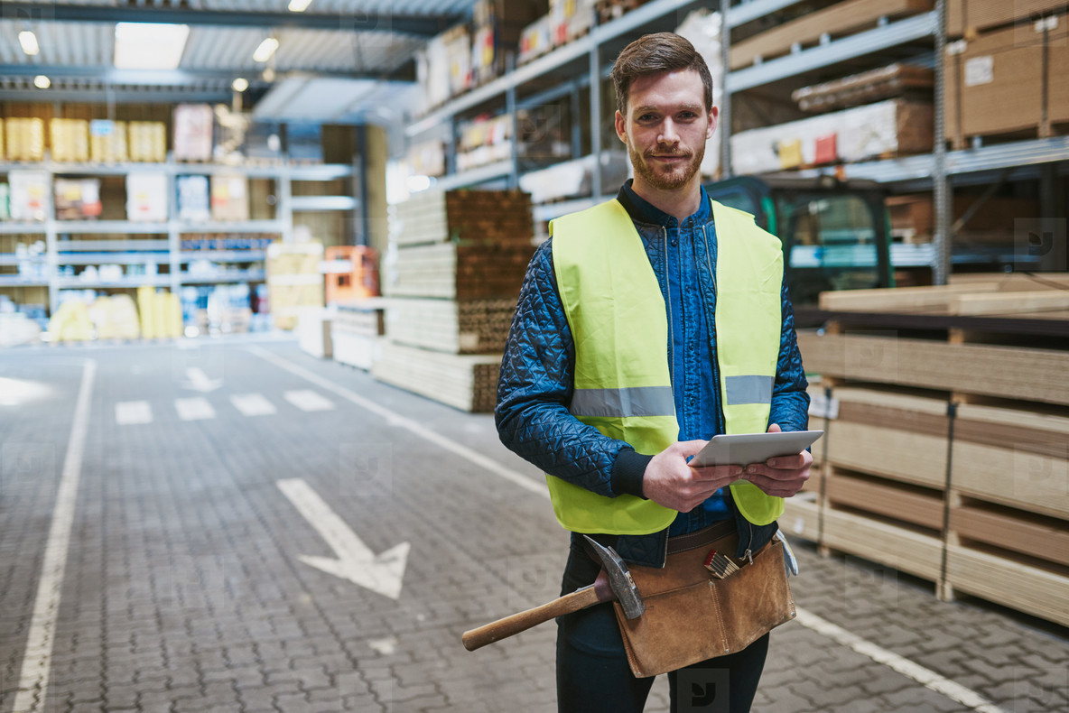 Handsome young handyman in a warehouse