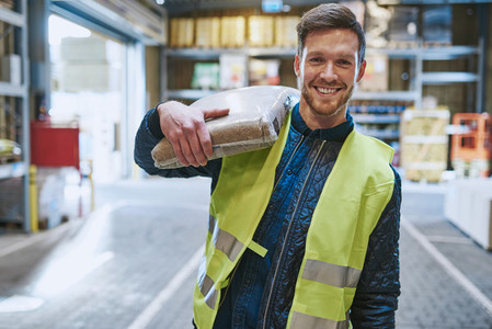 Smiling young man working in a warehouse