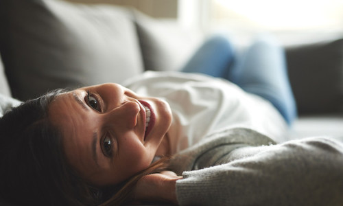 Woman laying on back with head tilted back smiling