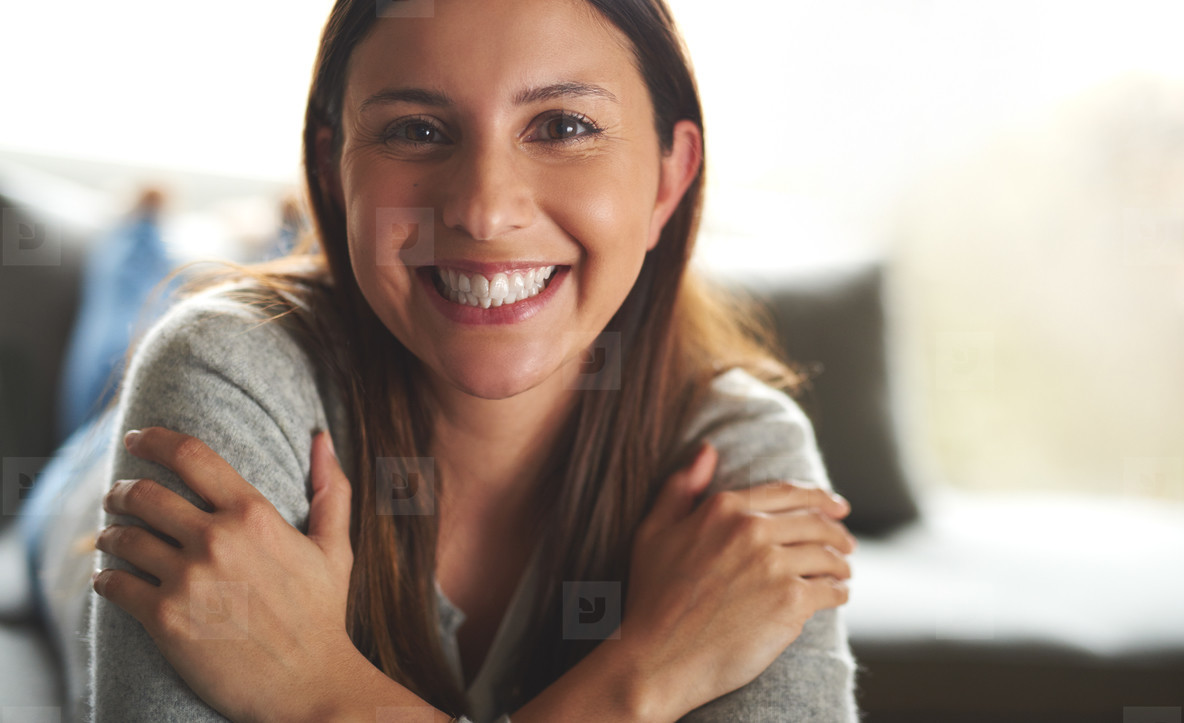 Woman laying on couch smiling widely