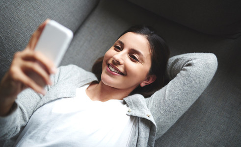 Woman laying on couch looking up at phone
