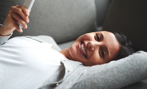 Woman laying on couch looking sideways smiling