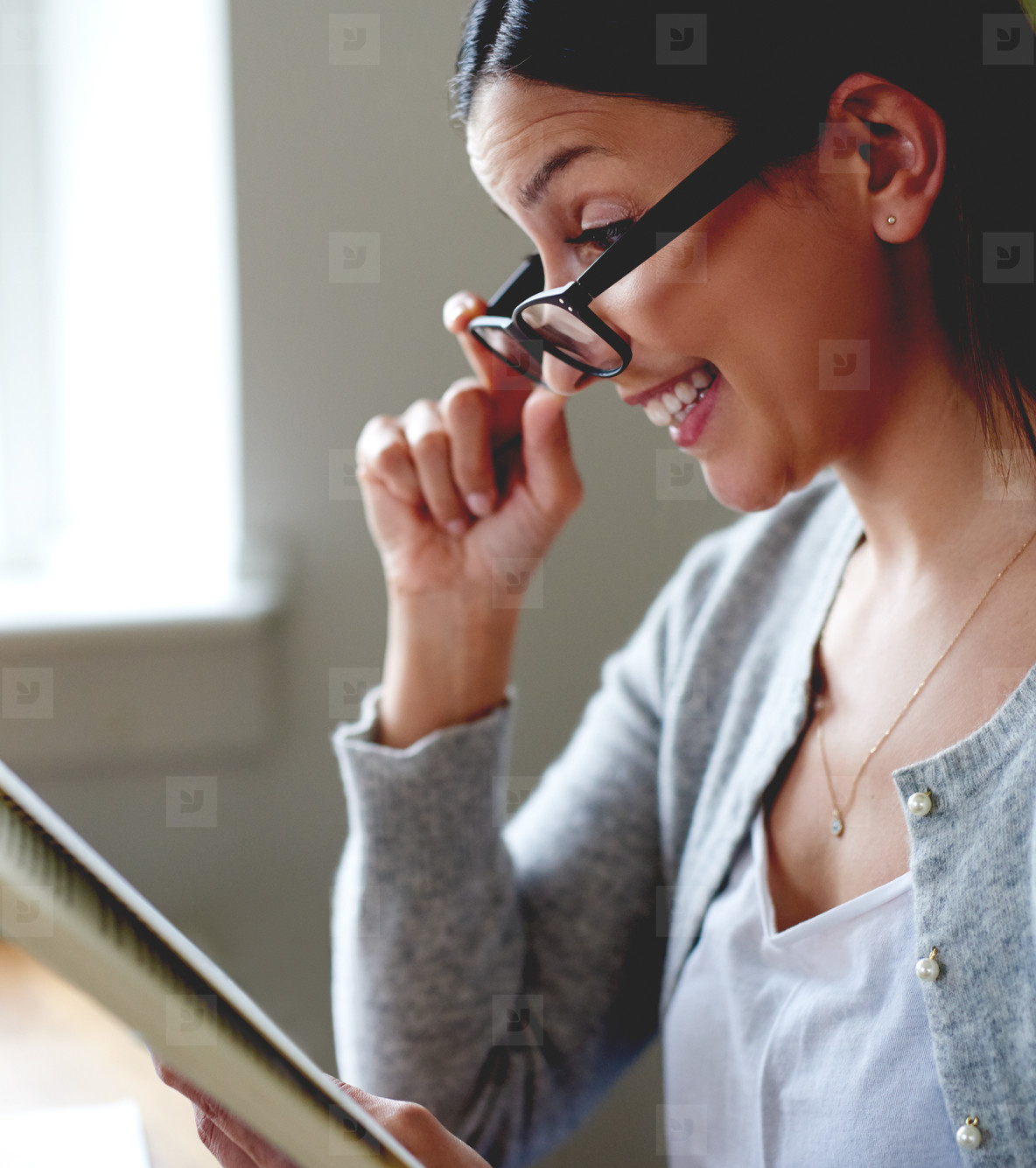 Woman pulling down glasses while reading book