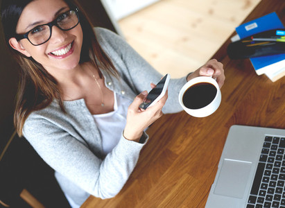 Woman looking up smiling holding mobile phone