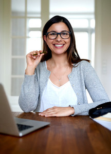 Woman sitting upright smiling at home office desk