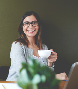 Woman smiling and drinking coffee