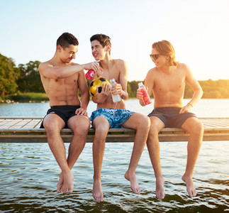 Three multiethnic teenage boys relaxing on a jetty