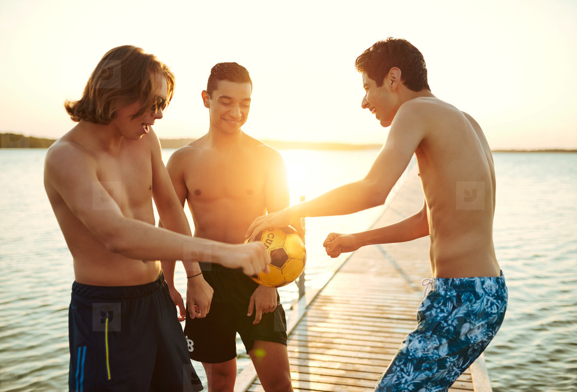 Three young teenage boys playing with a ball