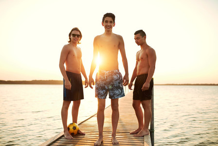 Three teenage boys on a jetty at sunset