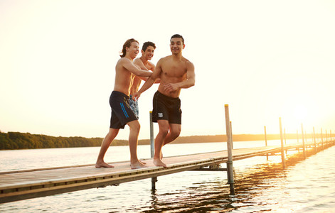 Two friends pushing a teenager into a lake