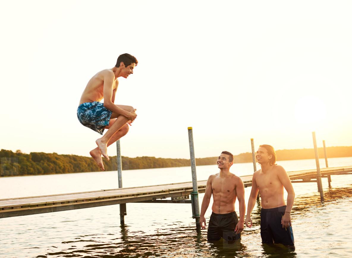 Teenage boy jumping into a lake