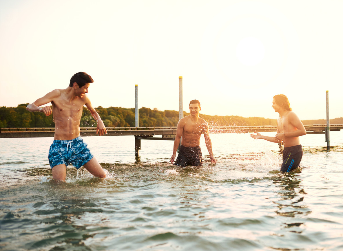 Three young teenage boys playing in a lake