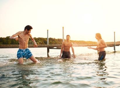 Three young teenage boys playing in a lake