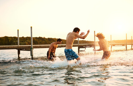 Three teenage boys playing in the water