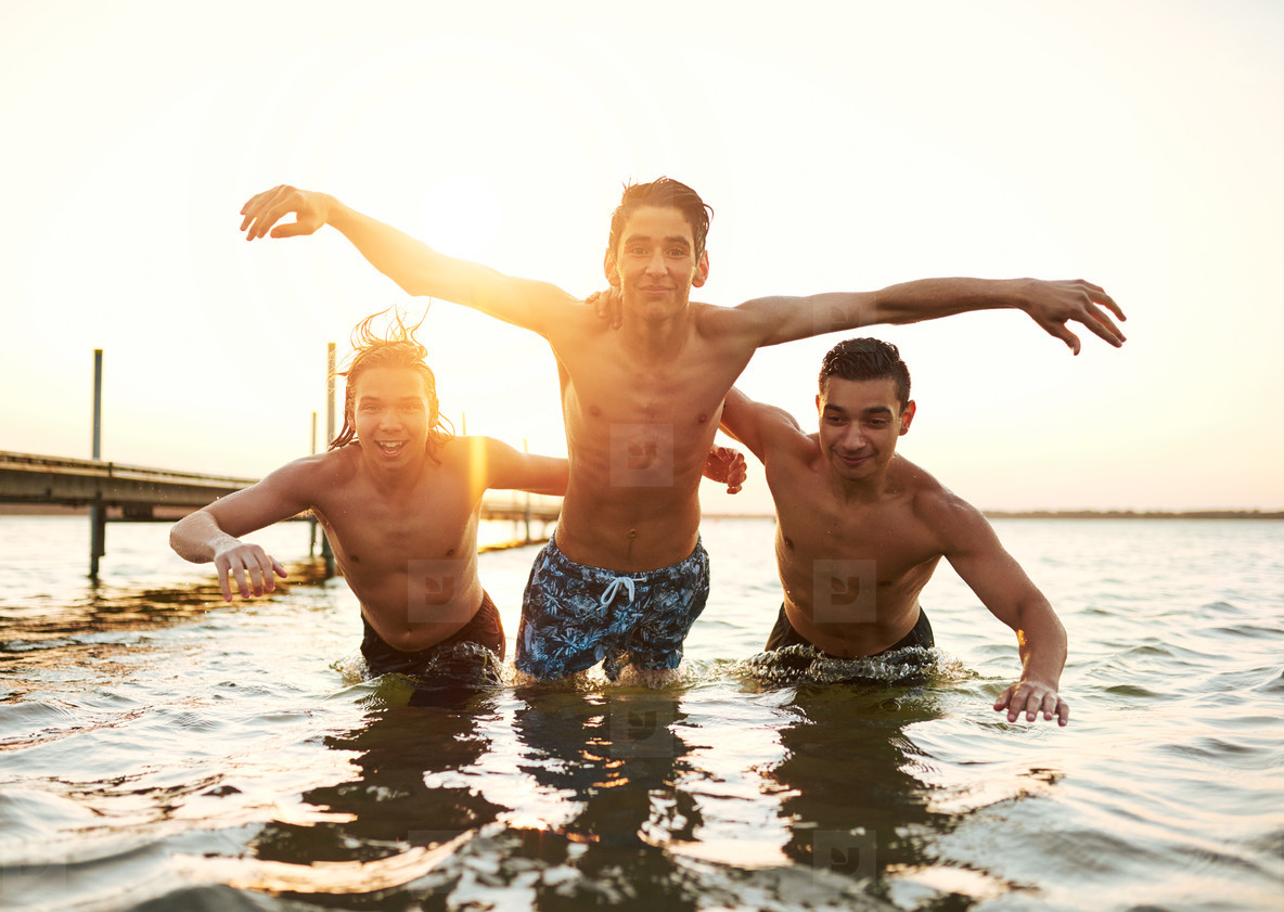 Three young men jumping in the water