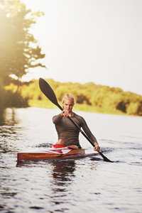 Athletic young woman paddling on lake in summer