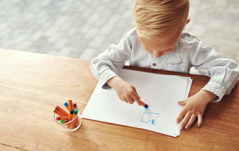Little boy drawing on an outdoor table