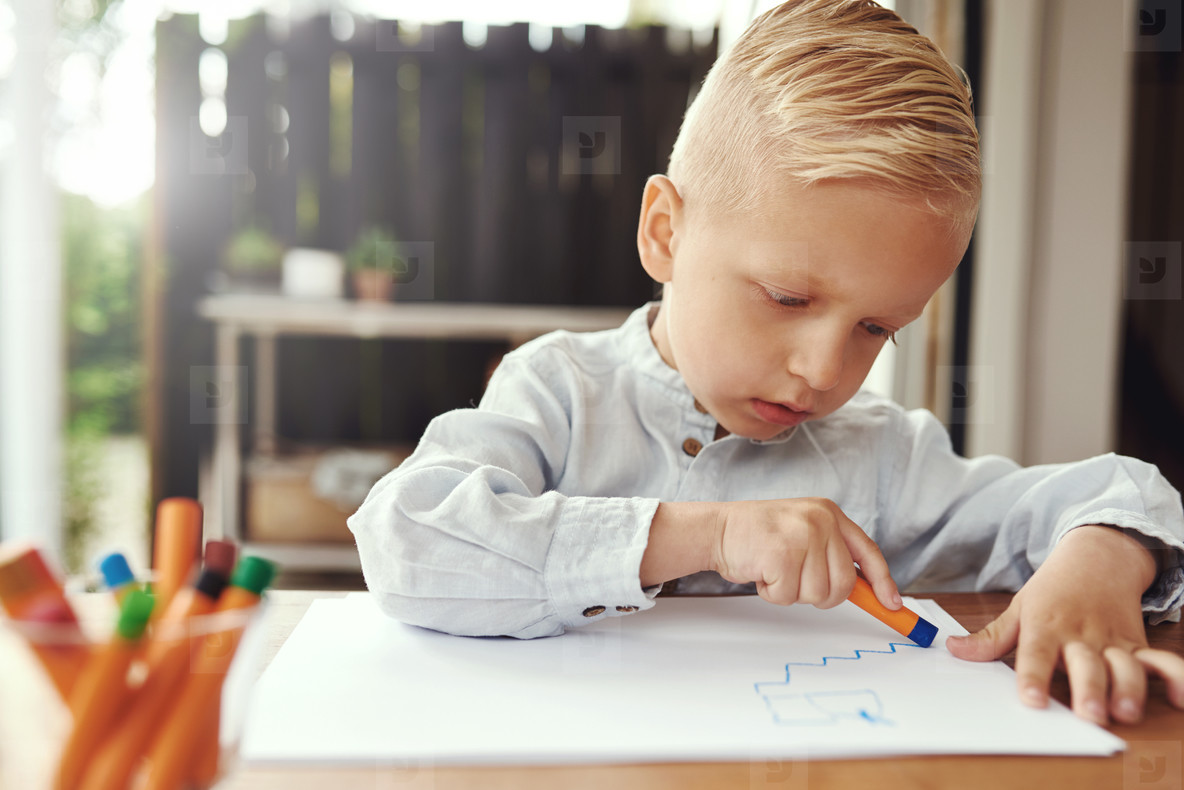 Handsome young boy drawing with crayons