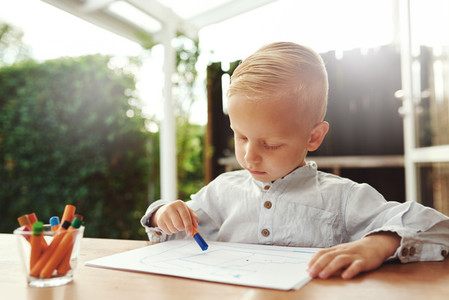 Little blond boy standing drawing with crayons