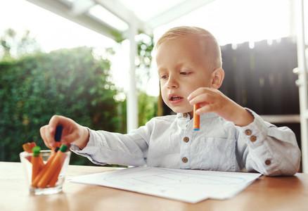 Cute little blond boy selecting a crayon