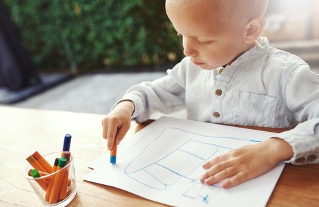 Small boy entertaining himself drawing