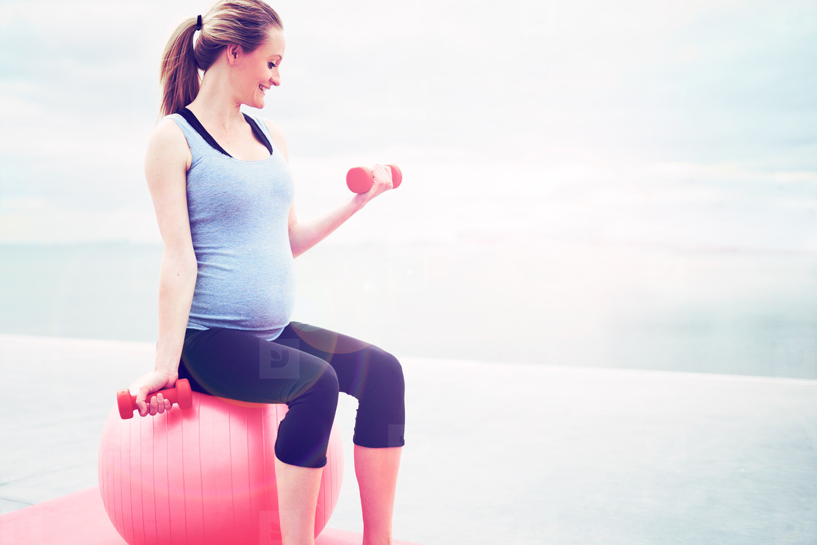 Pregnant woman doing fitness exercises