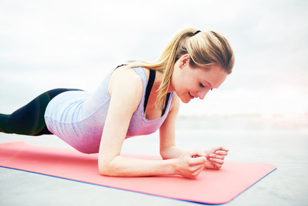 Smiling young woman working out during pregnancy
