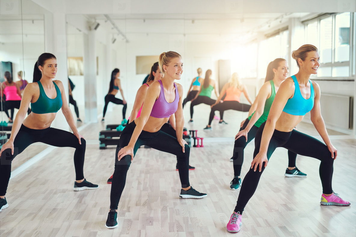 Group of women making squats in gym