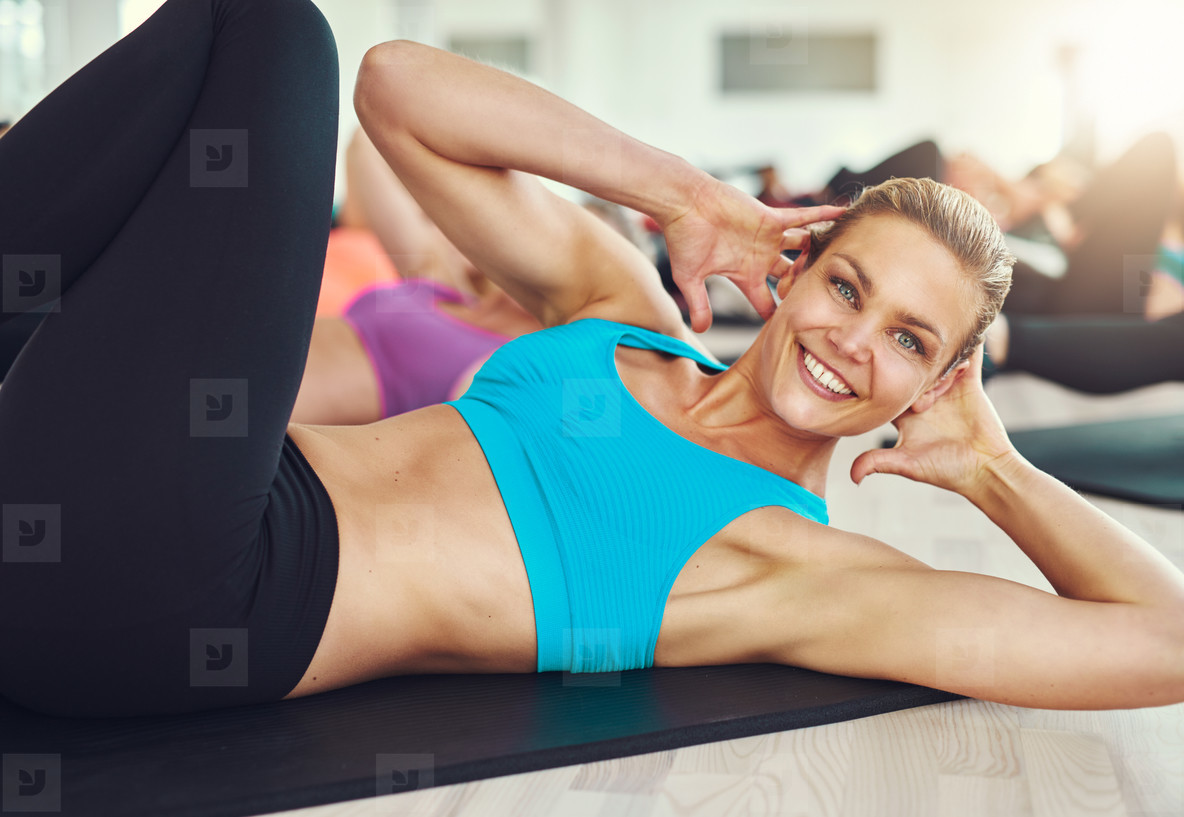 Smiling woman doing abdominal exercises on mat in gym