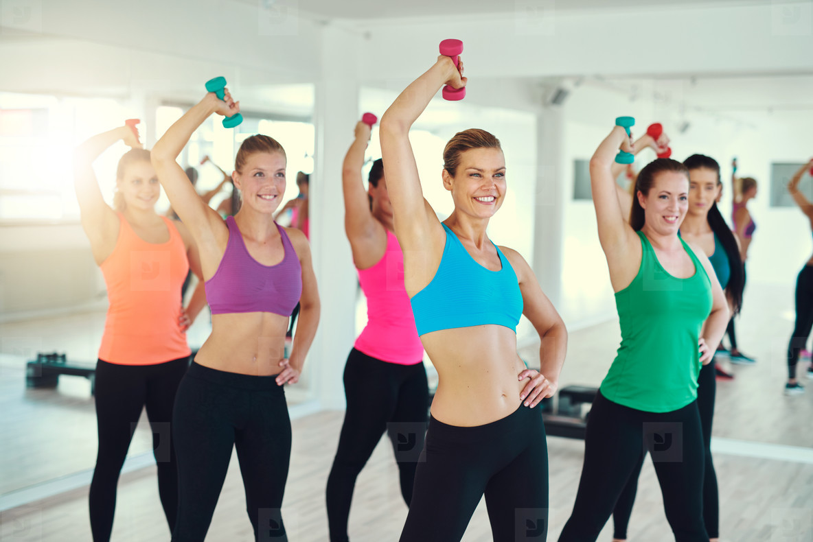 Close up of group of young women doing exercise with dumbbells on triceps