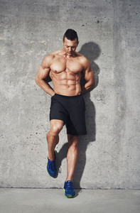 Fitness model standing against grey background  close up