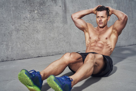 Male fitness model doing sit ups and crunches exercising abdominal muscles