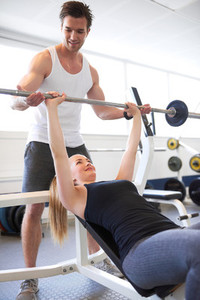 Athletic Guy Assisting Fit Girl Lifting Barbell