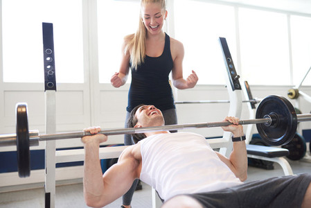 Woman Spotting Man Lifting Barbell in Gym