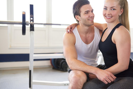 Couple Sitting with Arms Around Each Other in Gym