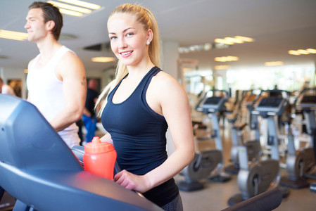 Fit Young Woman on Treadmill Smiling at Camera