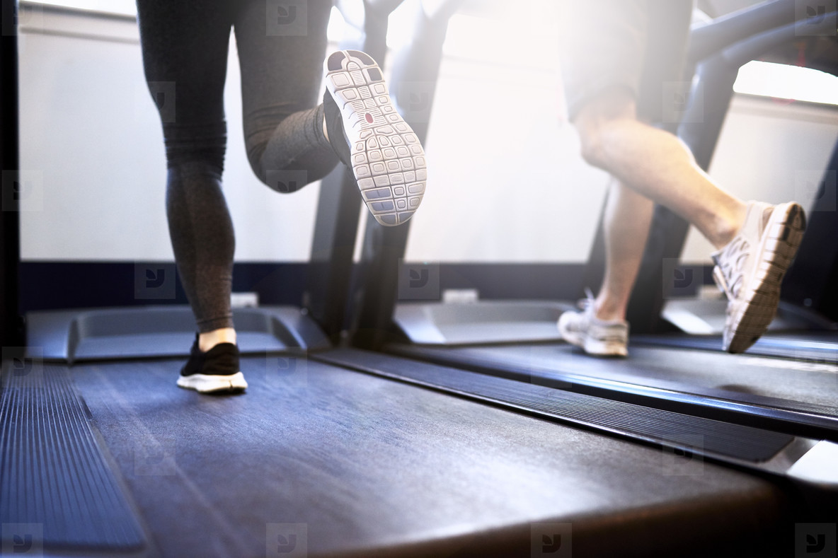 Legs of Fit Couple Exercising on Treadmill Device