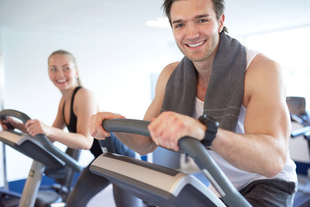 Muscular Guy on Elliptical Bike Smiling at Camera