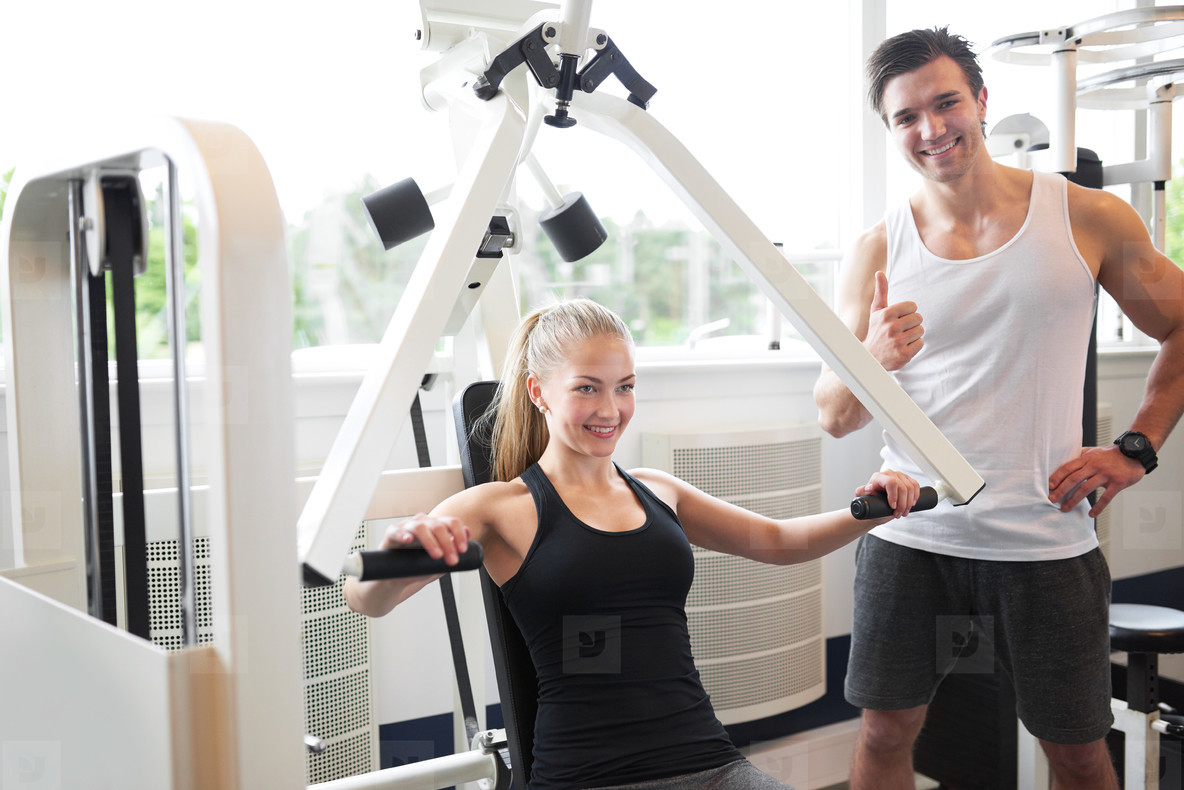 Trainer Assisting Woman Doing Chest Press Exercise