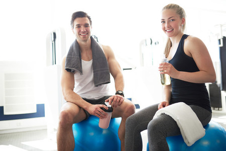 Active Young Couple In the Gym Smiling at Camera